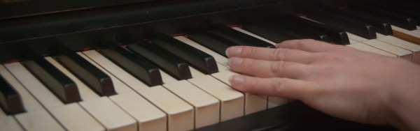 Een hand in close up op pianotoetsen